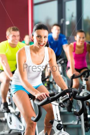 Группа молодых людей занимаются спортом на тренажерах в зале