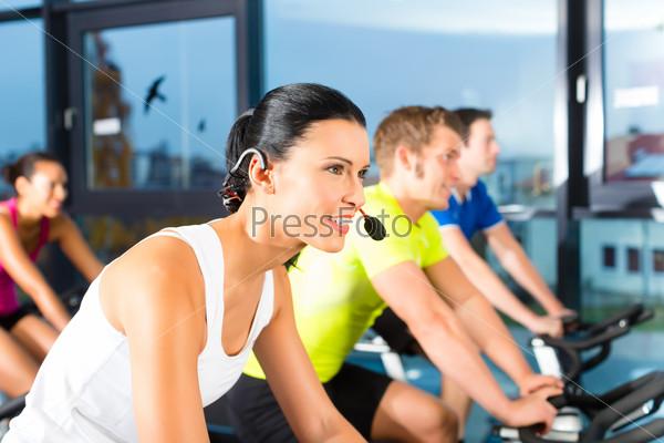 Молодые люди на тренажерах в фитнес-зале