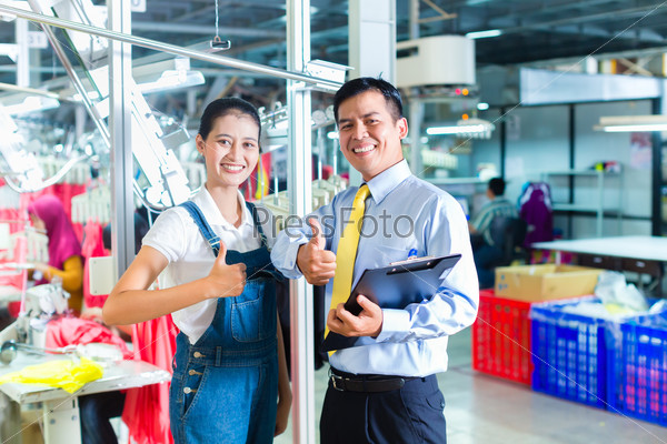 Asian foreman in textile factory giving training