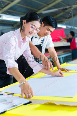 Asian production manager and designer in factory