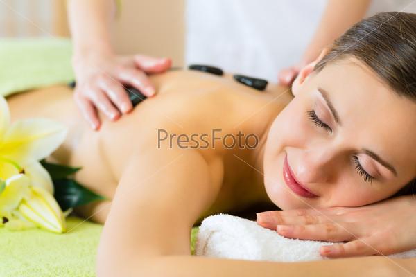 woman having wellness hot stone massage
