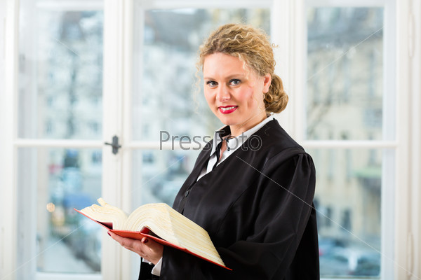 Lawyer in office with law book reading by window