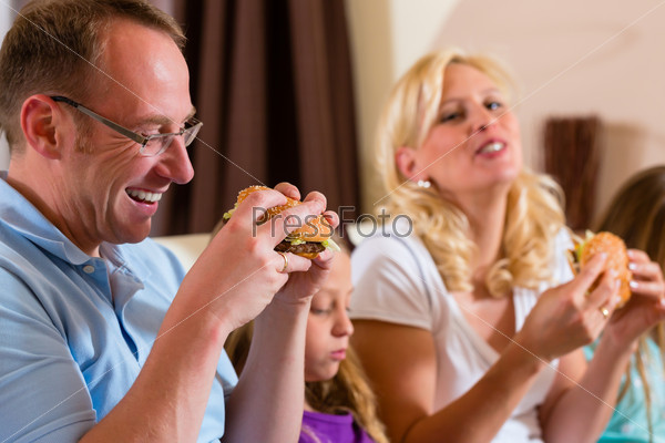 Family is eating hamburger or fast food
