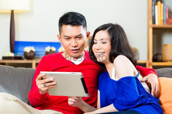 Индонезийская молодая пара с планшетным компьютером на диване