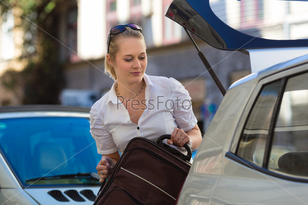 Woman loads suitcase into car boot or trunk