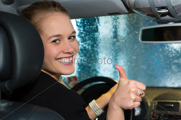 Young woman drives car in wash station