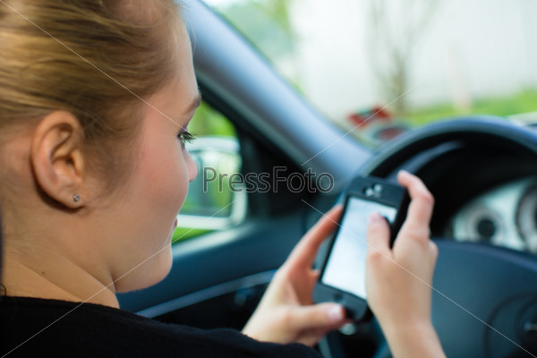 Young woman, in car with mobile phone