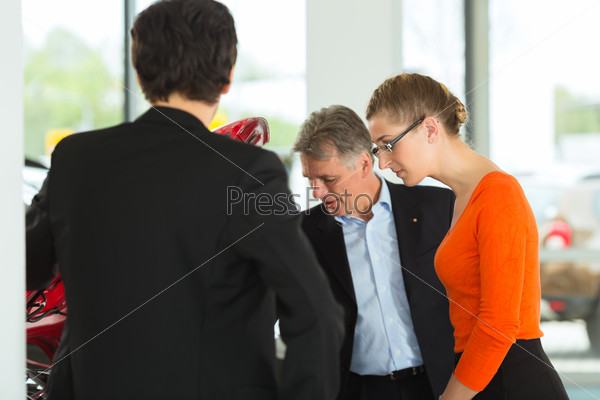 Mature man with young couple and auto in car dealership are looking beneath a hood