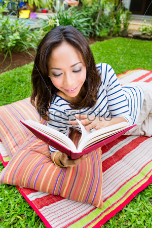 Asian woman at home in garden reading book