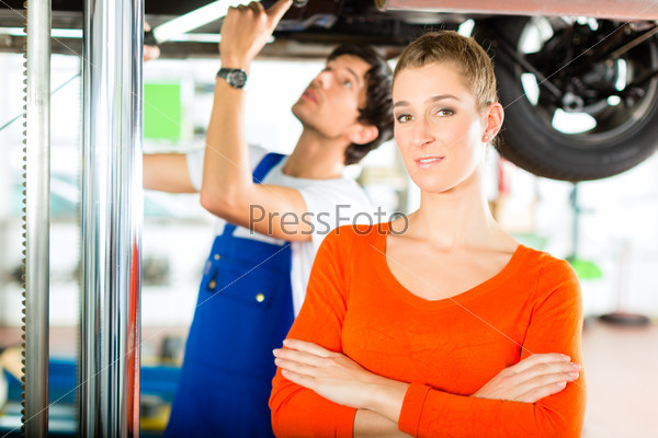 Car Mechanic repairing auto of woman customer