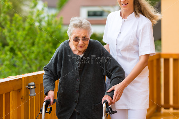 Young nurse and female senior with walking frame