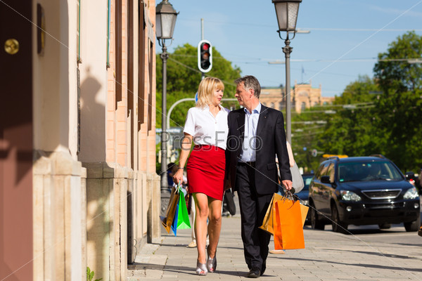 Mature couple strolling through city shopping in spring