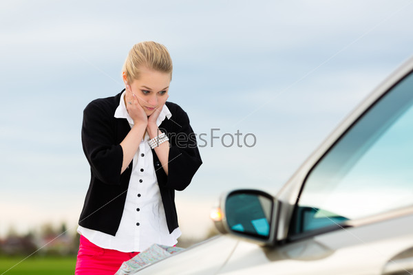 Young woman with map on car being lost