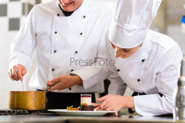 Chef team in restaurant kitchen with dessert
