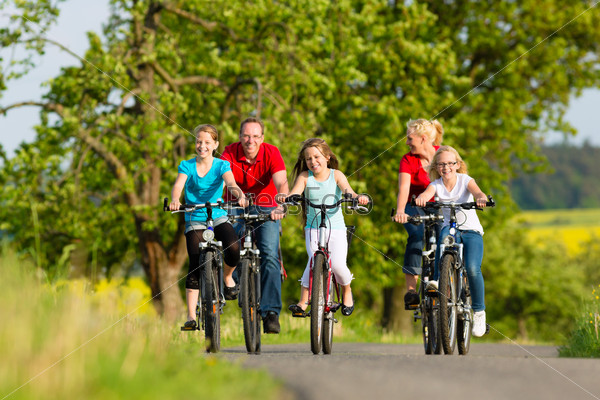 Family with kids cycling in summer with bicycles