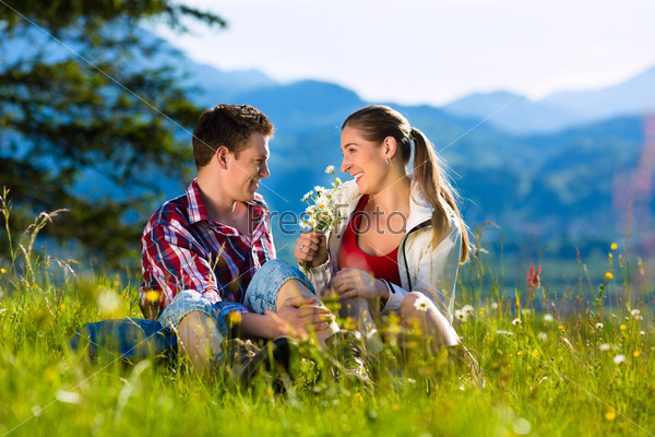 Couple is sitting in the meadow with mountain