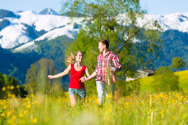 Couple running in the meadow with mountain