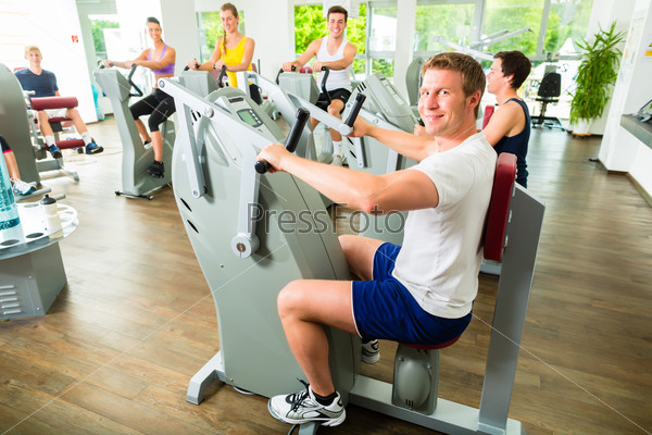 People in sport gym on machines