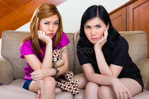 Two asian girls at home being bored or sad