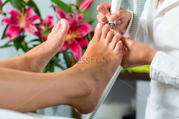 Woman in nail studio receiving pedicure