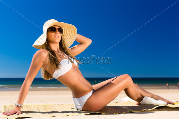 Attractive woman sitting in the sun on beach
