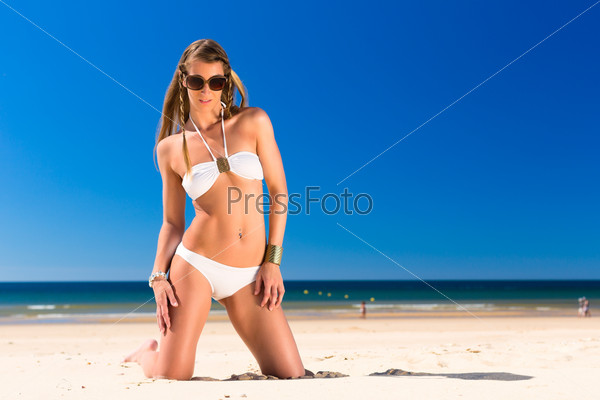 Attractive woman is kneeling  in the sun on beach