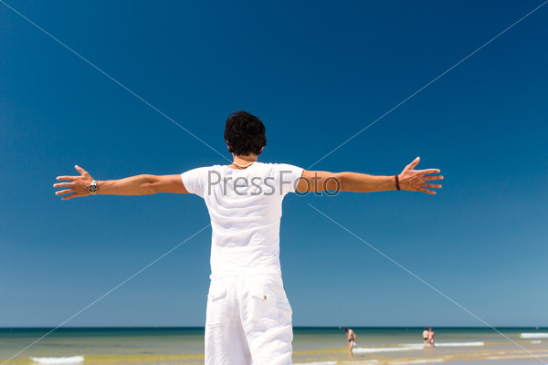 Handsome man standing in the sun on beach