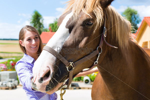 Young woman in the stable with horse and is happy