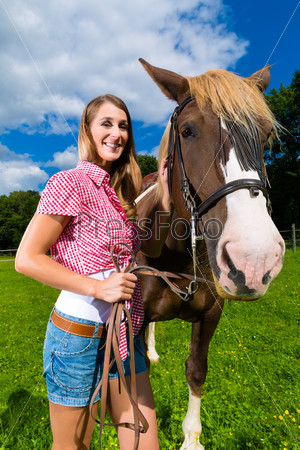 Young woman on the meadow with horse