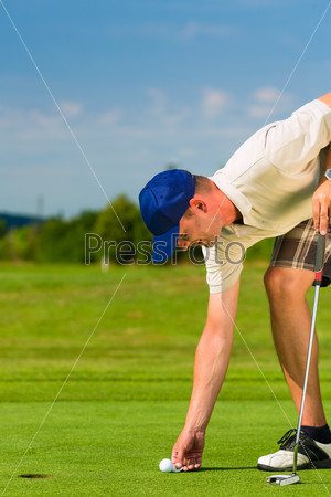 Young golf player on course putting