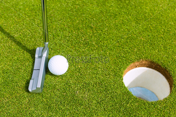 Golf player putting ball in hole