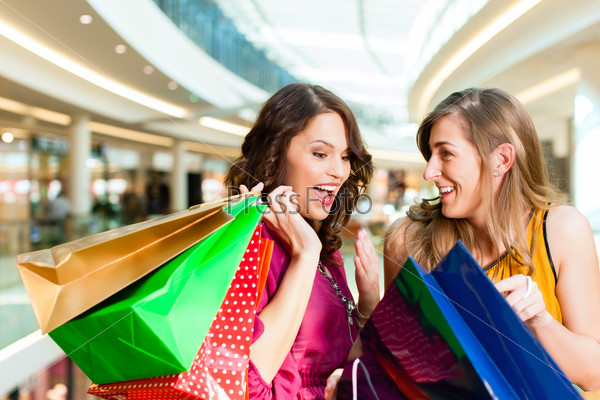 Two girls shopping in mall looking in bags
