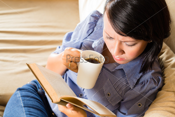 Asian girl with cup reading book