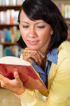 Asian girl in library reading a book