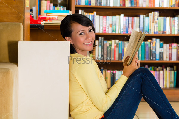 Young Girl in library reading book