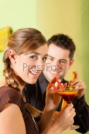 Young couple drinking cocktails in bar or restaurant