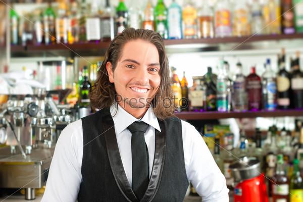Barista or barman behind his bar
