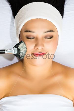 Cosmetics - Asian woman gets a facial mask