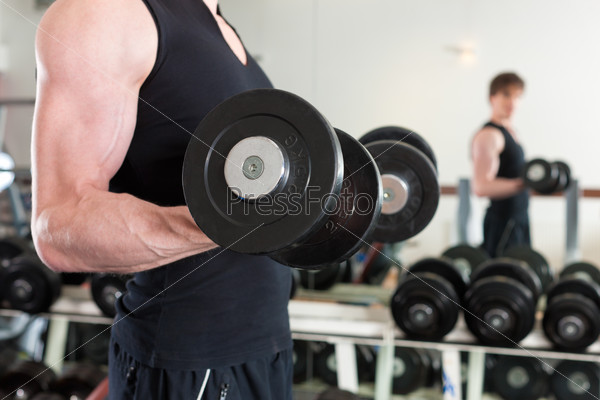 Sport - man is exercising with barbell in gym