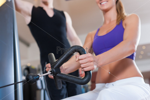Sport - couple is exercising on machines in gym