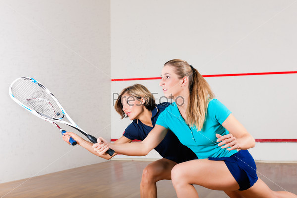 Squash sport - women playing on gym court