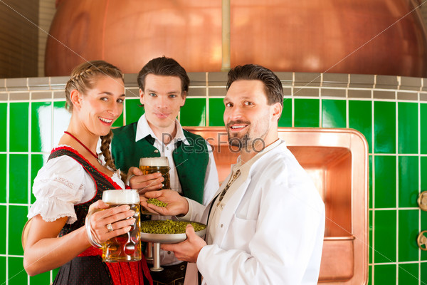 Couple with beer and their brewer in brewery