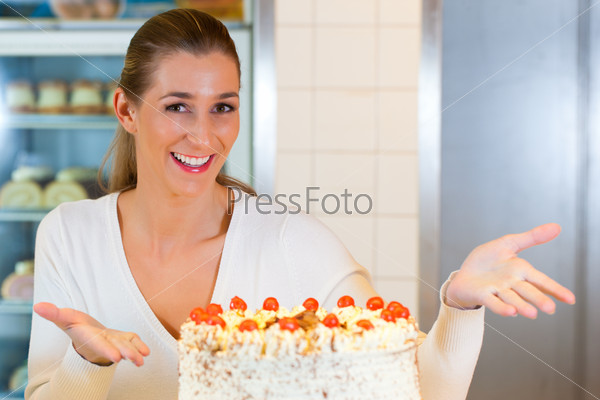 Female baker or pastry chef with torte