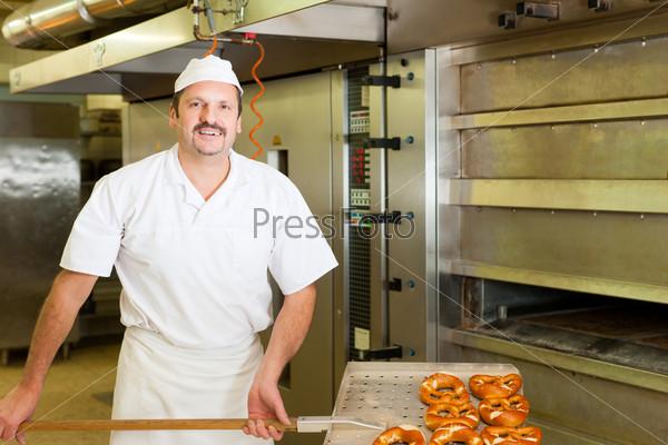 Baker in his bakery baking bread