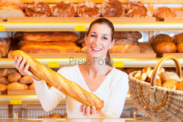 Female baker in her bakery with baguette