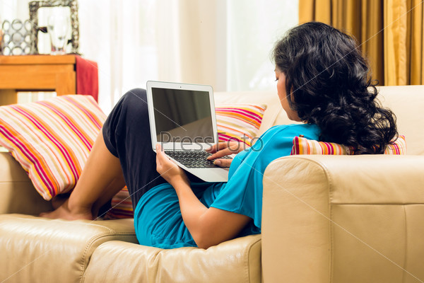 Asian Woman sitting on couch and surfing the internet