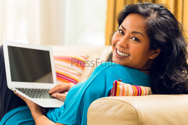 Asian Woman sitting on couch surfing the internet and smiling