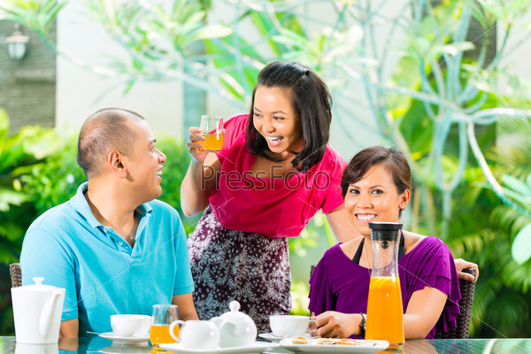 Asian friends having coffee on home porch