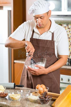 Asian man baking cake in home kitchen
