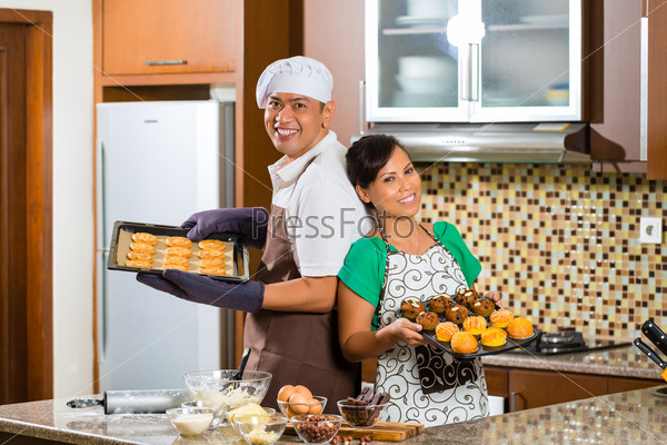 Asian couple baking cake in home kitchen